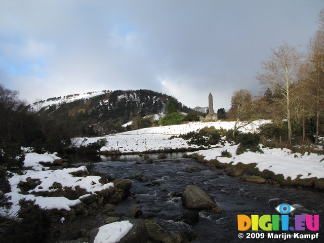 SX02580 Glendasan river in front of Round Tower Glendalough in snow