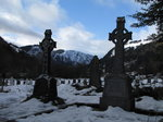 SX02789 Snow on celtic crosses in Glendalough with view to Lugduff mountain.jpg