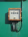 SX03024 Rusty box of switches on green wall.jpg