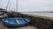 SX08684 Blue rowboat on resting near harbour wall.jpg