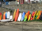 SX09003 Canoes and kayaks lined up against harbour wall.jpg