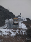 SX12143 Gritting truck driving through hillsides covered in snow.jpg