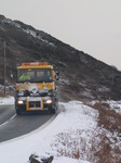 SX12145 Gritting truck driving through hillsides covered in snow.jpg