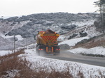 SX12146 Gritting truck driving through hillsides covered in snow.jpg
