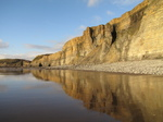 SX25591 Cliffs reflected in water on beach.jpg